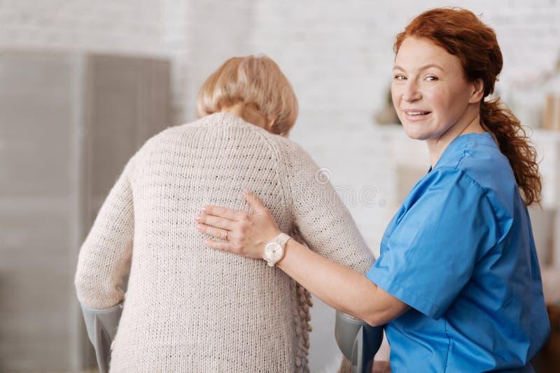 Mujer apacible agradable que toma cuidado de la señora madura imagen de archivo