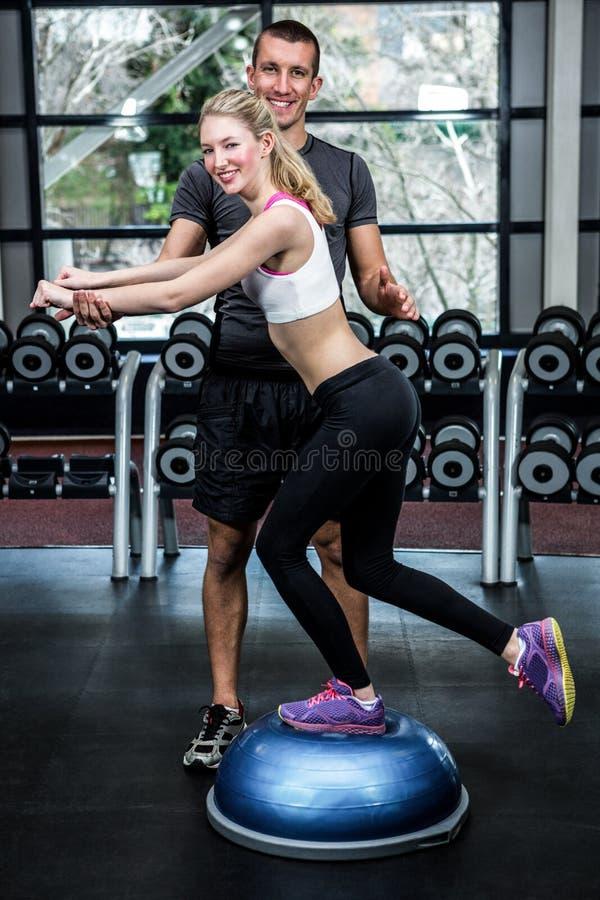 Mujer apta con el instructor que ejercita con bosu imagen de archivo libre de regalías