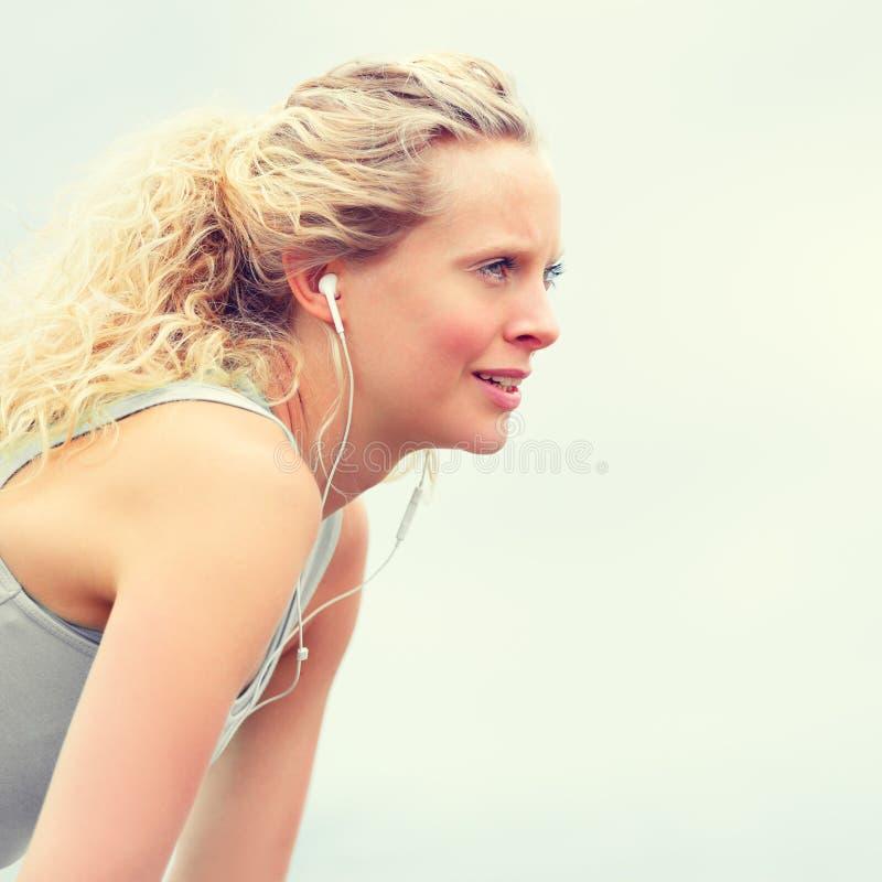 Mujer apta de los jóvenes activos que ejercita con los auriculares fotografía de archivo libre de regalías
