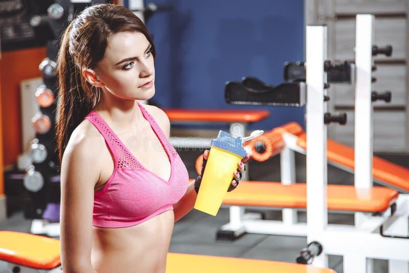 Mujer apta de los jóvenes con la bebida de la energía que se relaja y que bebe en el gimnasio Concepto del deporte y del fittness foto de archivo