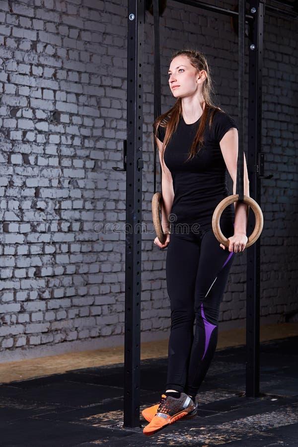 Mujer apta de los jóvenes en el sportwear que hace tirón-UPS en los anillos gimnásticos contra la pared de ladrillo en el gimnasi fotografía de archivo libre de regalías