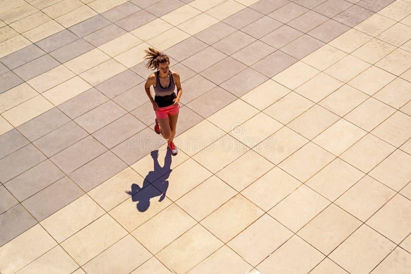 Mujer apta de los jóvenes que corre en día soleado en la ciudad imagenes de archivo