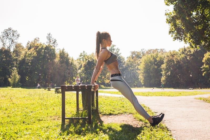 Mujer apta de los jóvenes que ejercita haciendo pectorales al aire libre fotografía de archivo libre de regalías