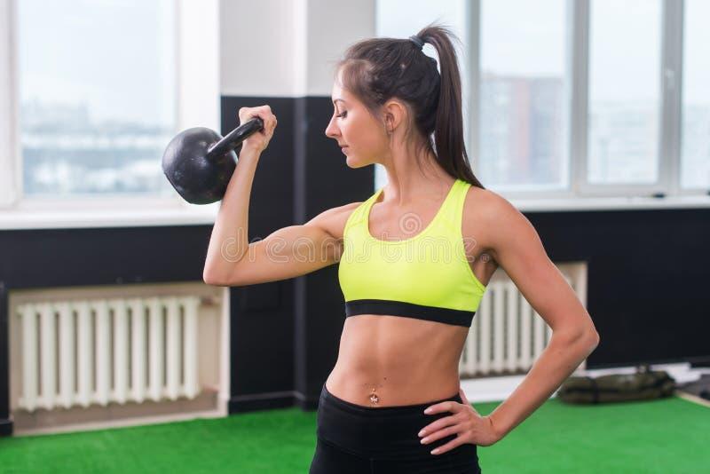 Mujer apta de los jóvenes que hace los ejercicios que levantan el kettlebell, resolviendo el bíceps, tríceps, músculos traseros foto de archivo libre de regalías