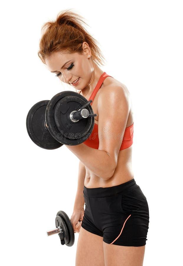 Mujer apta de los jóvenes que se resuelve con pesas de gimnasia fotos de archivo