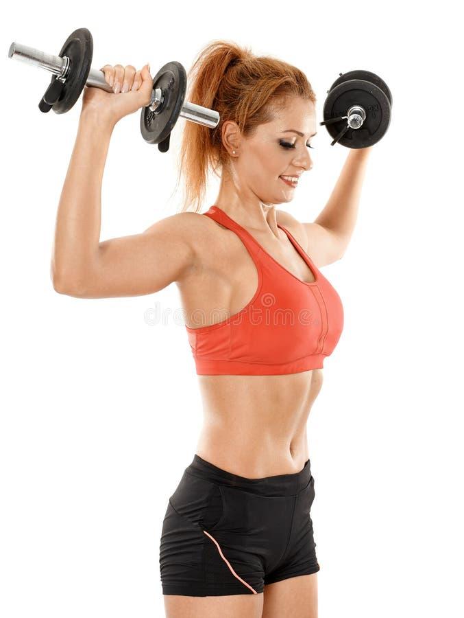 Mujer apta de los jóvenes que se resuelve con pesas de gimnasia foto de archivo