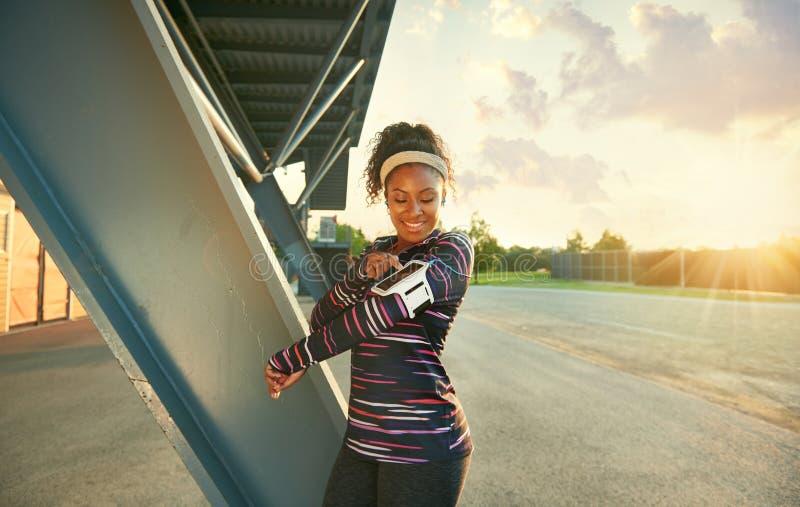 Mujer apta del afroamericano que elige música de un app para correr en la puesta del sol imágenes de archivo libres de regalías
