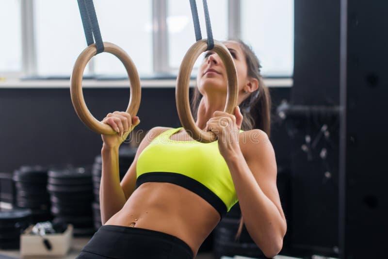 Mujer apta del atleta que ejercita en el gimnasio que levanta en los anillos gimnásticos fotos de archivo