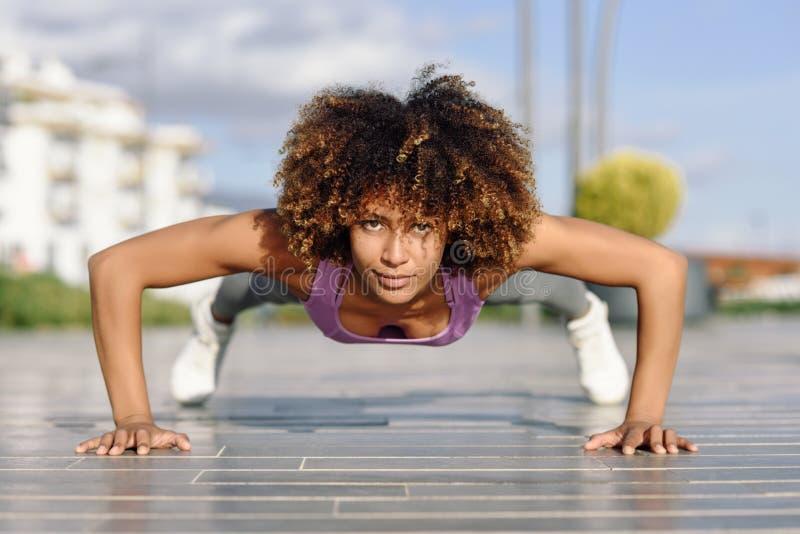 Mujer apta del negro que hace flexiones de brazos en piso urbano imagen de archivo libre de regalías