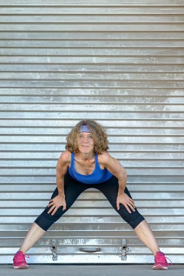Mujer apta deportiva que se resuelve haciendo estiramientos imagenes de archivo