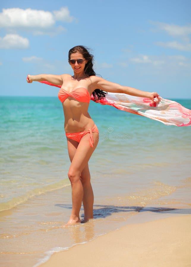 Mujer apta joven en el bikini y las gafas de sol que sostienen la bufanda que agita detrás de ella, mar tranquilo en fondo imagenes de archivo
