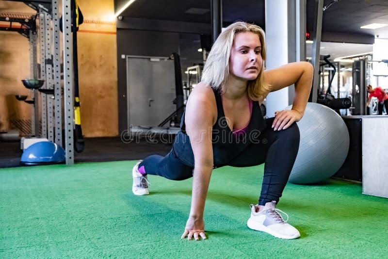 Mujer apta joven en el gimnasio que hace ejercicio inmóvil de la estocada Fema fotos de archivo