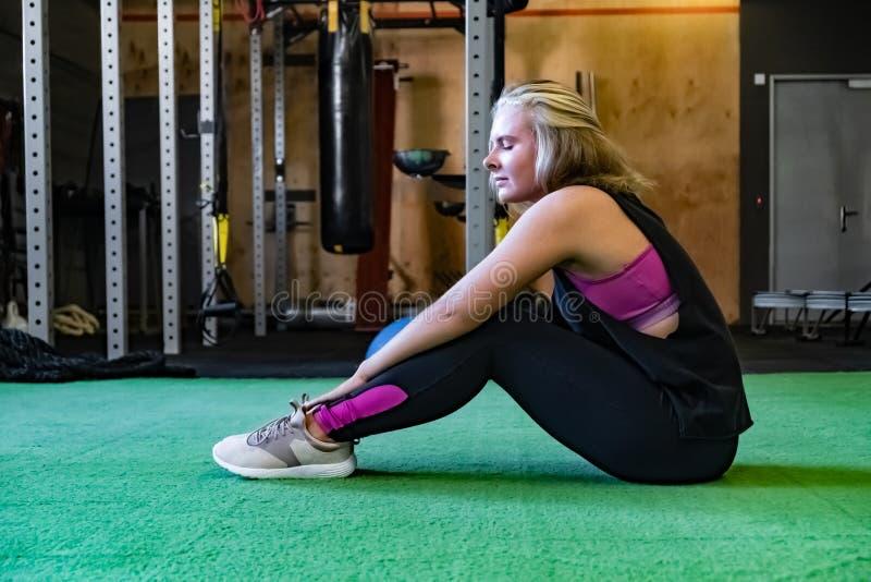 Mujer apta joven en el gimnasio que se sienta en la tierra y que toma resto fotos de archivo libres de regalías