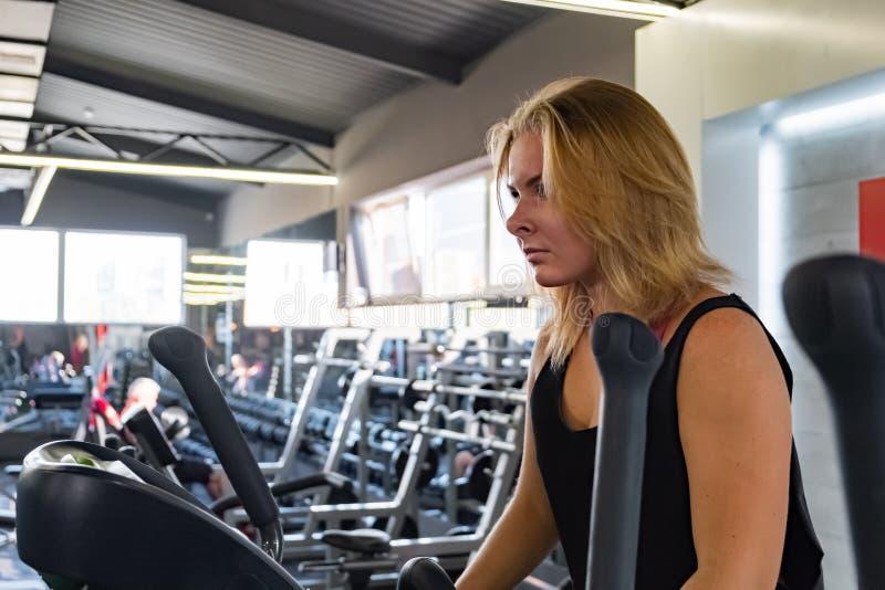 Mujer apta joven en el gimnasio usando instructor cruzado elíptico Femal fotos de archivo libres de regalías