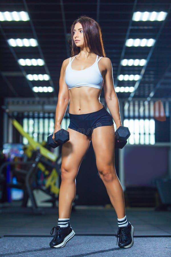 Mujer apta joven en pantalones cortos deportivos y pesas de gimnasia que se sostienen superiores mientras que se coloca en el gim foto de archivo