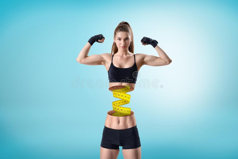 Mujer apta joven en top negro corto y pantalones cortos del gimnasio, en actitud doble del bíceps, corte del cuerpo superior en l fotografía de archivo libre de regalías
