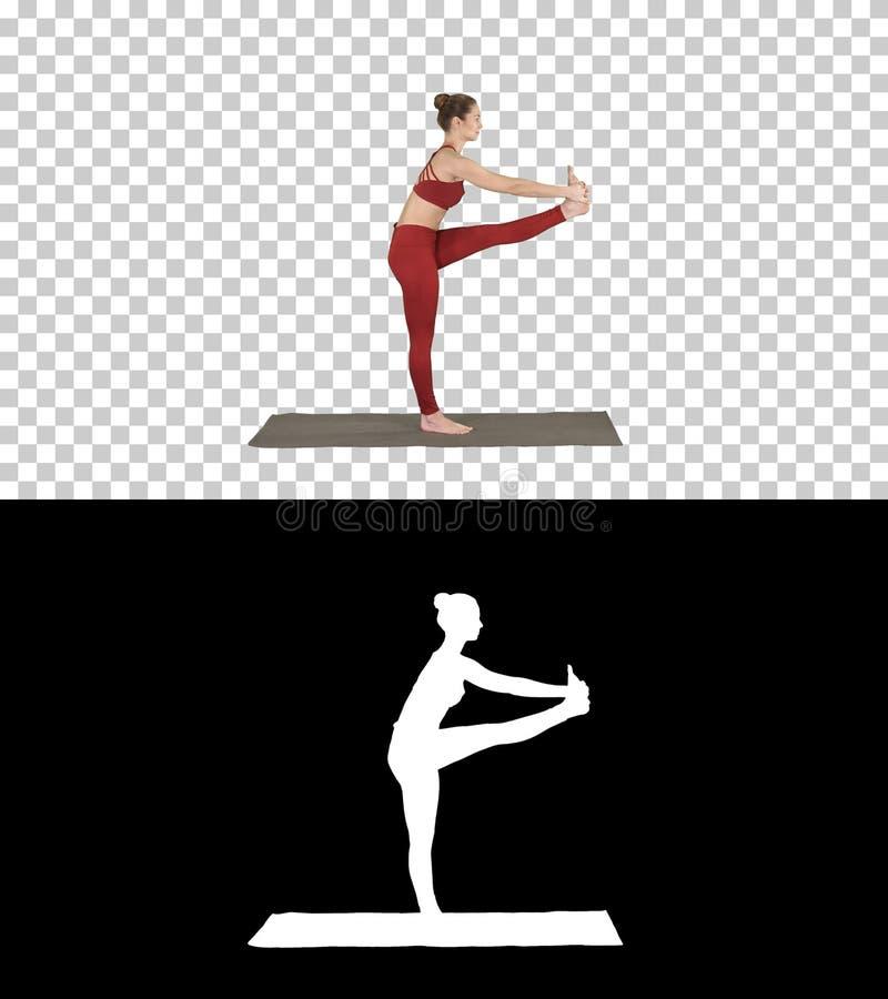 Mujer apta joven hermosa en la ropa de deportes que hace el ejercicio del deporte, doblando en la variación de Utthita Hasta Pada fotos de archivo libres de regalías