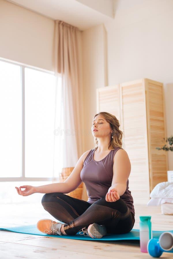 Mujer apta pacífica hermosa que intenta meditar imagen de archivo libre de regalías