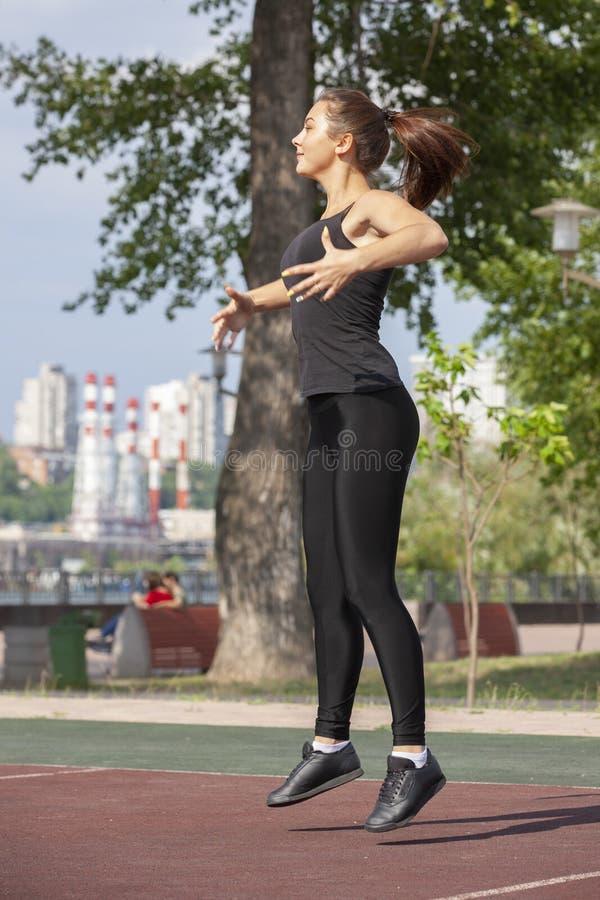 Mujer apta que ejercita al aire libre, forma de vida y concepto sanos del ejercicio imagen de archivo