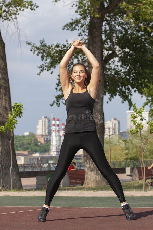 Mujer apta que ejercita al aire libre, forma de vida y concepto sanos del ejercicio imágenes de archivo libres de regalías