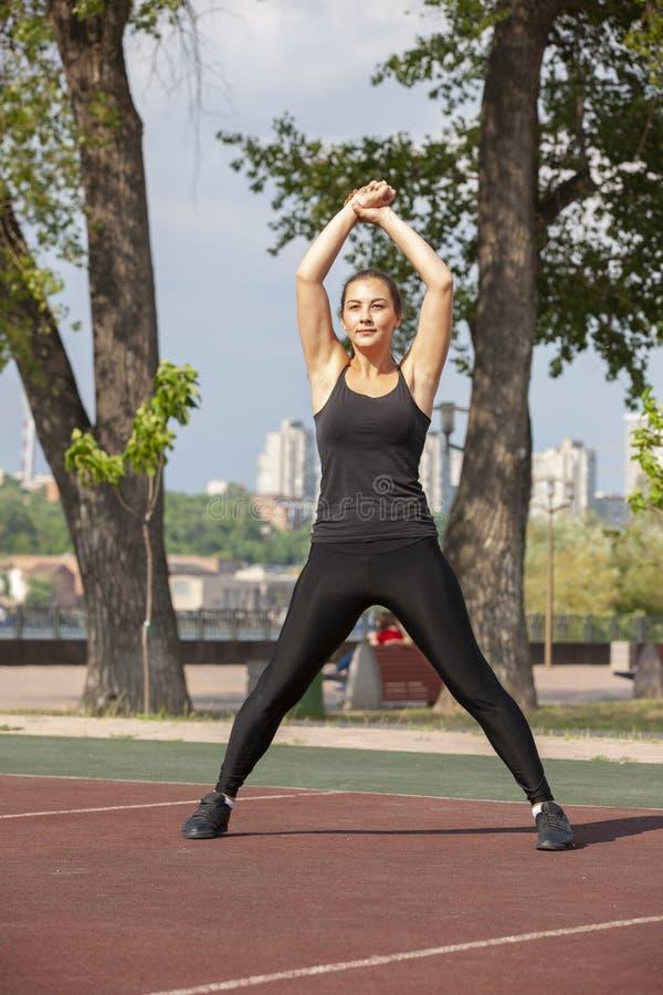 Mujer apta que ejercita al aire libre, forma de vida y concepto sanos del ejercicio imagenes de archivo