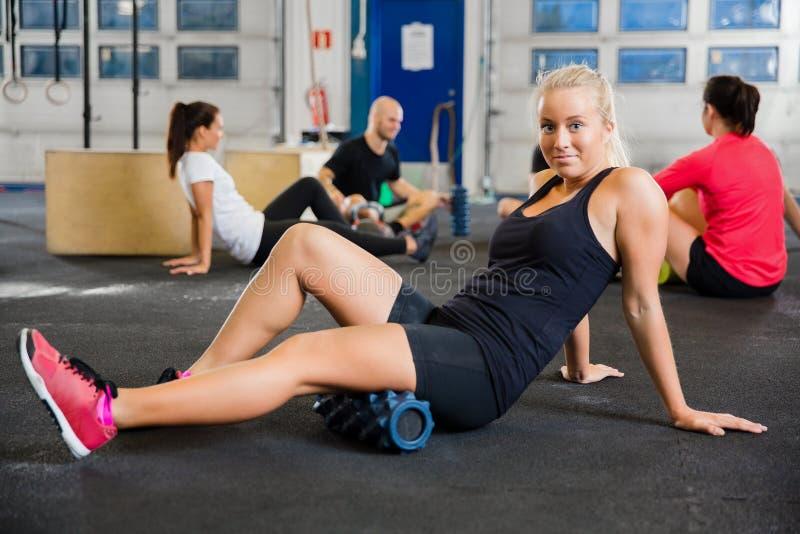 Mujer apta que ejercita con el rodillo de la espuma en club de salud imagen de archivo