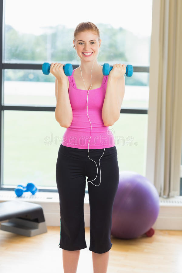 Mujer apta que ejercita con pesas de gimnasia en estudio de la aptitud fotografía de archivo