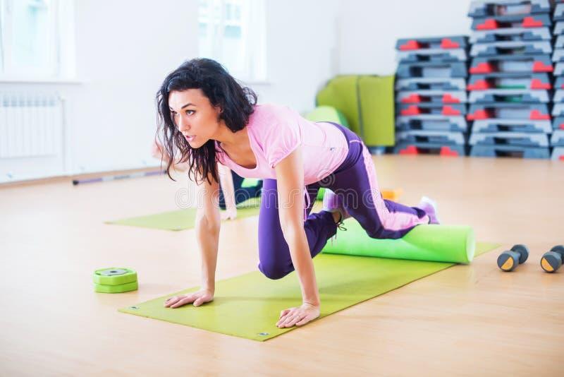 Mujer apta que ejercita haciendo entrenamiento de la base en club de fitness fotografía de archivo