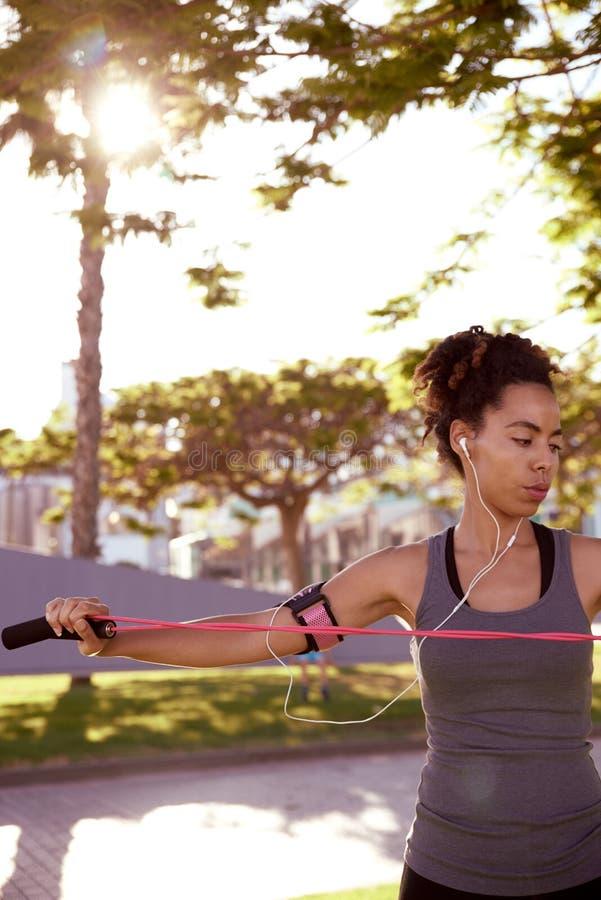 Mujer apta que estira con la cuerda de salto imagenes de archivo