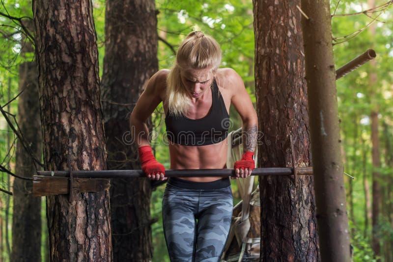 Mujer apta que hace el músculo para arriba en barra horizontal imagen de archivo