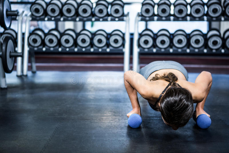 Mujer apta que hace pectorales con pesas de gimnasia imagen de archivo libre de regalías