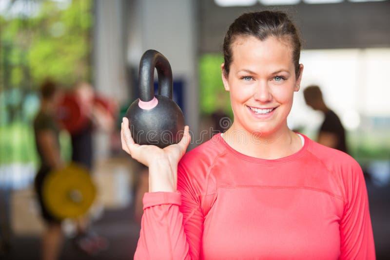 Mujer apta que levanta Kettlebell en el gimnasio imágenes de archivo libres de regalías