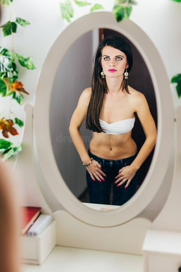 Mujer apta que mira en espejo imagen de archivo