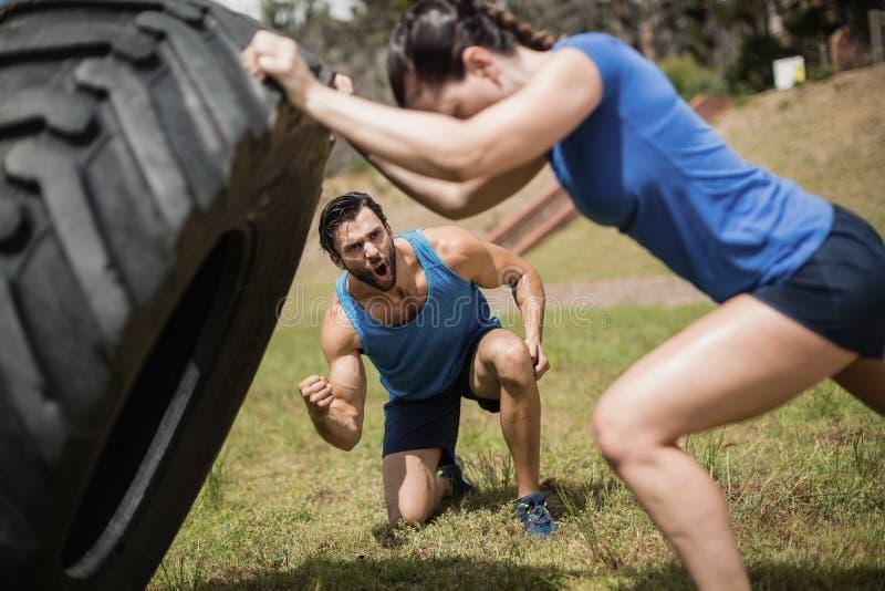 Mujer apta que mueve de un tirón un neumático mientras que instructor que anima durante carrera de obstáculos imágenes de archivo libres de regalías