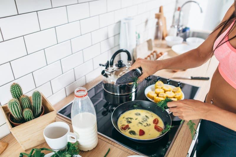 Mujer apta que prepara el desayuno sano en cocina fotografía de archivo libre de regalías