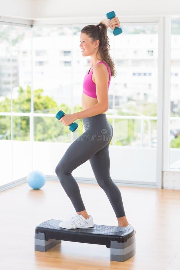Mujer apta que realiza ejercicio de los aeróbicos del paso con pesas de gimnasia fotos de archivo