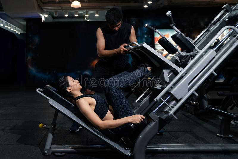 Mujer apta que se resuelve con el instructor en el gimnasio, mujer que hace el entrenamiento del músculo en el gimnasio Atleta qu imágenes de archivo libres de regalías