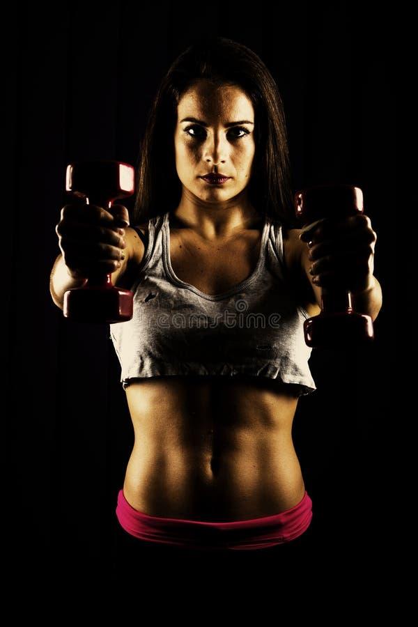 Mujer apta que se resuelve con pesas de gimnasia imagen de archivo