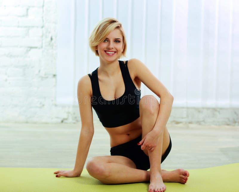 Mujer apta que se sienta en la estera de la yoga imagen de archivo