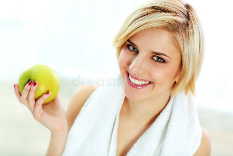 Mujer apta sonriente feliz que sostiene la manzana verde imagen de archivo libre de regalías