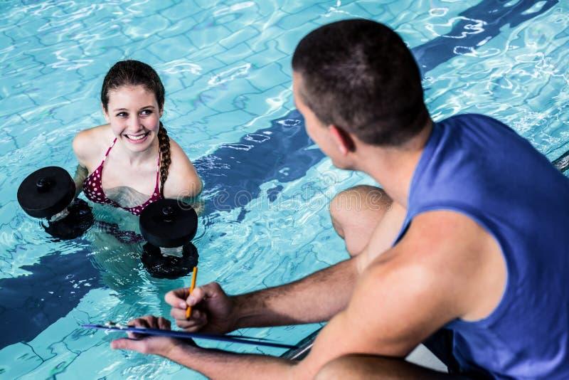 Mujer apta sonriente que hace aeróbicos de la aguamarina imagenes de archivo
