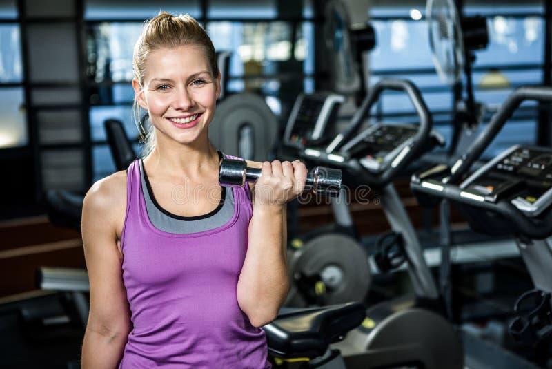 Mujer apta sonriente que hace ejercicio de las pesas de gimnasia imágenes de archivo libres de regalías
