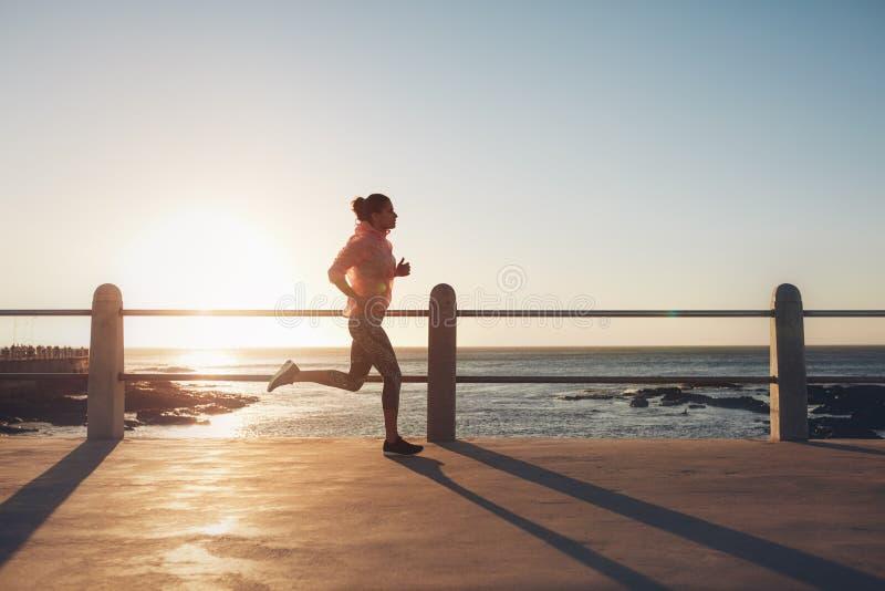 Mujer apta y joven que corre en el camino de la playa foto de archivo libre de regalías