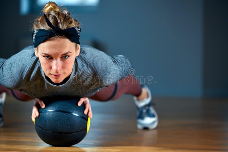 Mujer apta y muscular con los ojos de perforación que hacen entrenamiento intenso de la base con el kettlebell en gimnasio Ejerci foto de archivo