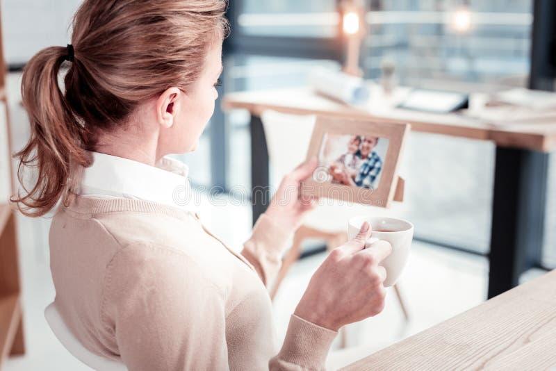 Mujer apuesta alegre que disfruta del tiempo del té que se sienta en sala de estar imagen de archivo