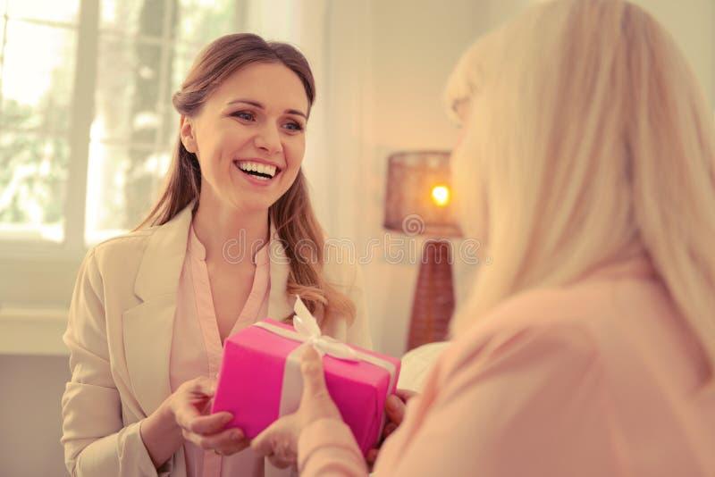 Mujer apuesta alegre que toma una caja de regalo fotografía de archivo