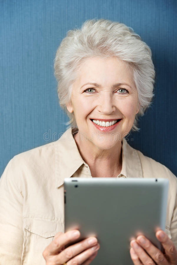 Mujer apuesta mayor que sostiene una tableta de la PC foto de archivo