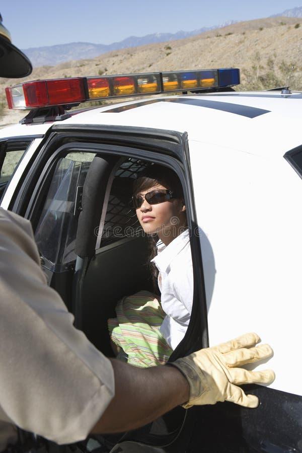Mujer arrestada que se sienta en coche policía imagen de archivo