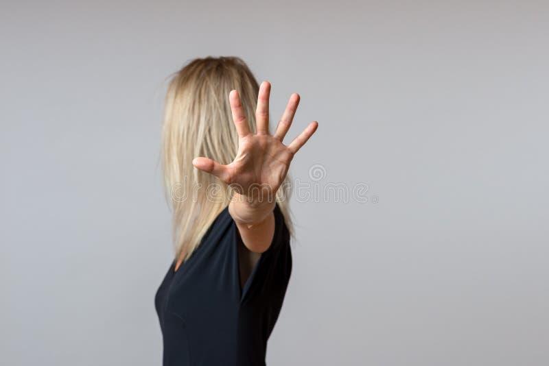 Mujer arrogante imperiosa que gesticula con su mano foto de archivo