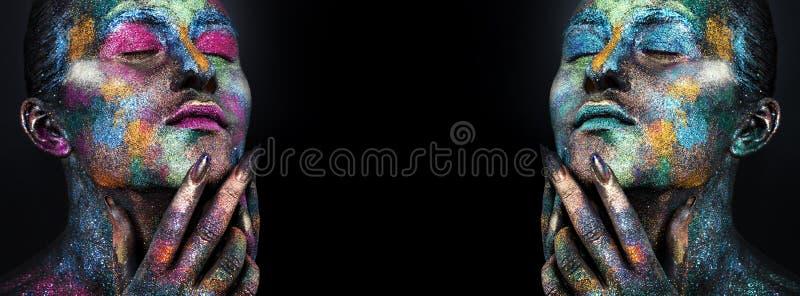Mujer artística joven en pintura negra y polvo colorido Maquillaje oscuro que brilla intensamente Arte de cuerpo creativo en el t foto de archivo